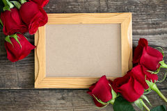 Photo frame and red roses on wooden background Stock Photo