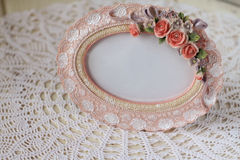 Photo frame in a romantic vintage style. On a table with a white lace tablecloth Royalty Free Stock Photos