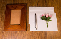 The photo frame, roses, envelope and pen. Workplace of the businessman. Stock Photography