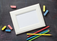 Photo frame and school supplies on blackboard background Royalty Free Stock Photography
