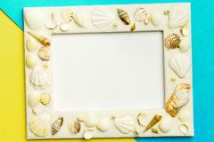 Photo frame with shells on turquoise and yellow color paper texture background. The concept of a summer vacation.  Summer Flatlay. Image, abstract, beach royalty free stock photos