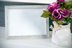 Photo frame stands on a shelf next to the flowers Stock Photography