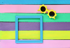 Photo frame and sunglasses on colorful wooden background. Royalty Free Stock Photography