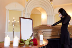 Photo frame and woman crying at coffin at funeral Stock Photos