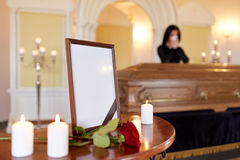 Photo frame and woman crying at coffin at funeral Royalty Free Stock Photography