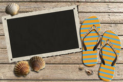 Photo Frame on Wooden Boardwalk with Sand. Aged photo frame with seashells on beach, flip flops sandals on wooden floor with sand Stock Photo