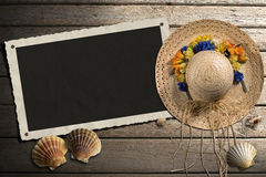 Photo Frame on Wooden Boardwalk with Sand. Aged photo frame with seashells on beach, straw hat with flowers on wooden floor with sand Stock Image