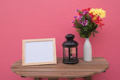 Photo Frame on a wooden and Flowers in jar and Lantern on pink background . Royalty Free Stock Photography