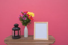 Photo Frame on a wooden and Flowers in jar and Lantern on pink background . Royalty Free Stock Images