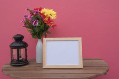 Photo Frame on a wooden and Flowers in jar and Lantern on pink background . Stock Photos