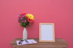 Photo Frame on a wooden table and book and Flowers in jar on pink background . Stock Photo