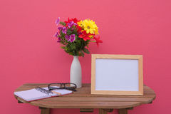 Photo Frame on a wooden table and book and Flowers in jar on pink background . Royalty Free Stock Photo