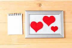 Photo frames, blank card and handmade hearts over wooden background Royalty Free Stock Images