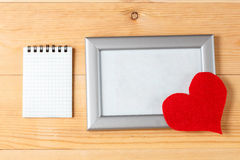 Photo frames, blank card and handmade hearts over wooden background Stock Image