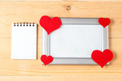 Photo frames, blank card and handmade hearts over wooden background Royalty Free Stock Image