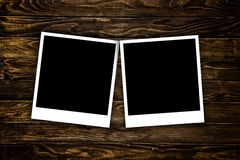 Photo frames. Blank polaroid photo frames over a wooden background stock image