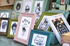 Photo frames on a Christams market fair with funny message about cat and home. Colorful pink, green, blue, white vintage wood photo frames with funny or stock photos