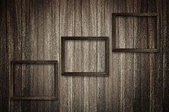 Photo frames on dark wooden wall Stock Photos