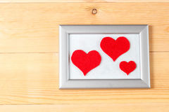 Photo frames and handmade hearts over wooden background Stock Photography