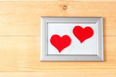 Photo frames and handmade hearts over wooden background Stock Photos