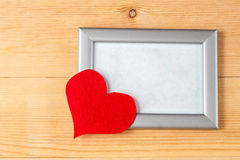 Photo frames and handmade hearts over wooden background Stock Image