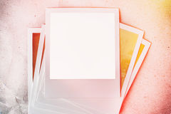 Photo frames on paper background with sun flare and warm light. Stock Photo