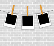 Photo frames on rope with clothespins on brick wal Stock Images