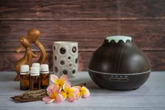Brown essential oil diffuser with frangipani flowers, candle and small wooden love statue stock image