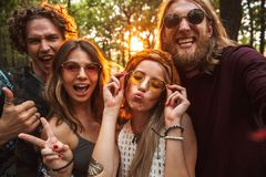 Photo of friendly hippie people men and women, smiling and taking selfie in forest. Photo of friendly hippie people men and women smiling and taking selfie in royalty free stock image