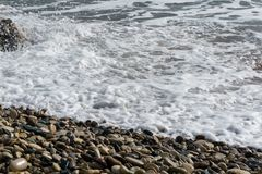 Photo of frothy sea, pebble. By day Royalty Free Stock Photo
