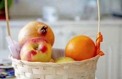 Fruits lie in a wicker basket in the bright kitchen stock image