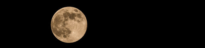 Photo of full-moon with soft yellow color an visible craters. Horizontal banner photo of full moon. Moon with nice soft yellow color. Visible craters on the edge Royalty Free Stock Photography