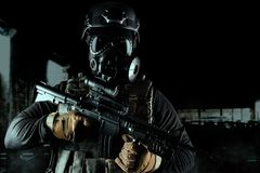 Warrior soldier in gas mask and rifle on black background