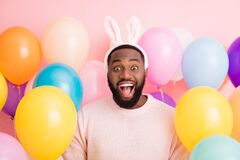Photo of funny dark skin guy colorful decorations easter party festive mood open mouth wear sweater fluffy bunny ears on