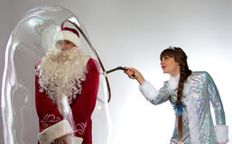 Photo funny Santa and snow maiden with soap bubble Royalty Free Stock Image