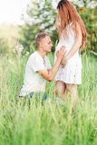 Future father hugs and kisses his wife`s pregnant belly. Photo of Future father hugs and kisses his wife`s pregnant belly stock image