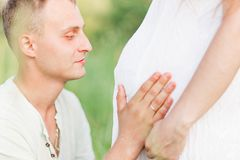Future father hugs and kisses his wife`s pregnant belly. Photo of Future father hugs and kisses his wife`s pregnant belly stock images