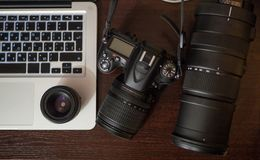 Photo gear on working place. DSRL, telephoto and laptop above Royalty Free Stock Photo