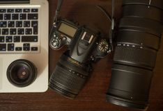 Photo gear on working place, telephoto. Photo gear on working place. DSRL, telephoto and laptop above Stock Photos
