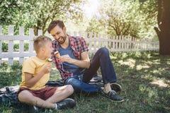 Photo gentille de deux types s'asseyant sur la couverture en parc Ils ont le crème dans des mains L'homme donne son fils pour ess photos stock