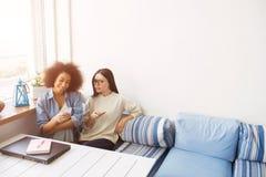 Photo gentille des étudiants s'asseyant près de l'un l'autre sur le sofa Ils tiennent des téléphones dans leurs mains Fille afro- Photos stock