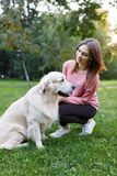 Photo of girl with dog on lawn in summer park Stock Photos
