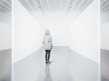 Photo of girl in empty modern gallery looking at the blank canvas. Royalty Free Stock Photography