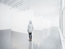 Photo of girl in empty modern gallery looking at the blank white canvas. Big windows, spotlights, concrete floor Stock Image