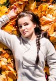 The girl lies on the autumn leaves royalty free stock image