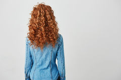 Photo of girl with red curly hair standing back to camera over white background. Copy space. Photo of young girl with red curly hair standing back to camera Royalty Free Stock Image