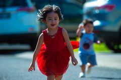 Photo of Girl in Red Dress Running on Street Stock Photos