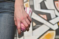 Photo of a girl`s hand with aerosol paint cans in hands on a graffiti wall background. The concept of street art and use of. Aerosol paints. Graffiti art shop royalty free stock photos