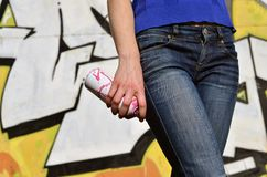 Photo of a girl`s hand with aerosol paint cans in hands on a graffiti wall background. The concept of street art and use of aerosol paints. Graffiti art shop royalty free stock photography