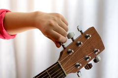Photo of girl`s hand tuning acoustic guitar, close-up. Photo of girl`s hand tuning guitar, close-up Stock Photo